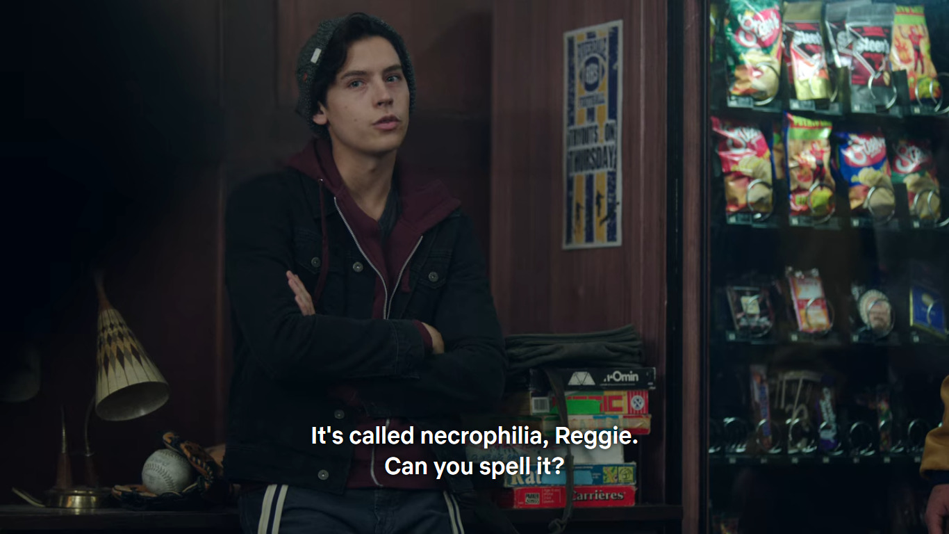 """Jughead Jones is leaning against a drawer next to a vending machine. He's saying: """"It's called necrophilia, Reggie. Can you spell it?"""""""